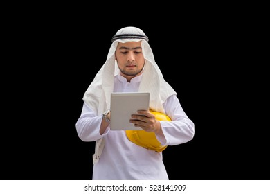 Construction and maintenance concept, Arab Middle Eastern architect holding yellow helmet and checking tablet PC with black background