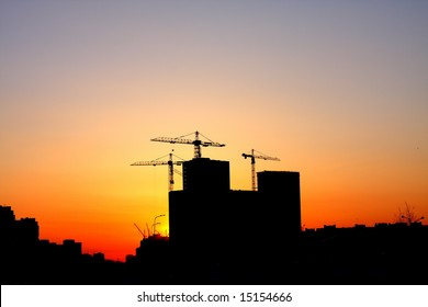 Construction of a major housing project at sunset.
