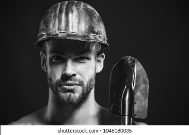 Construction male worker portrait holds sapper shovel. Labour, occupation, engineer, industry man, repairman, builder or miner wears protective helmet holds shovel. Closeup. Copy space. Black & white.