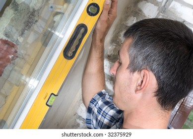 A construction man checking the level of a wall
