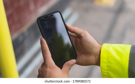 construction man holding a mobile on site. Man pointing on smartphone screen, chatting in social networks, site meeting, social distancing, meeting website and sending sms, text messenger on site.