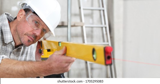 construction man worker measure with level laser wear hard hat and protective glasses  at interior building site