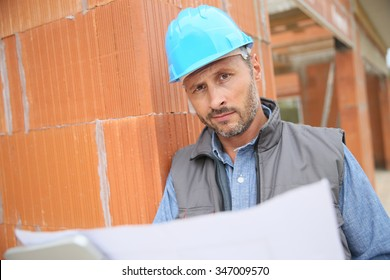 Construction manager checking blueprint on site