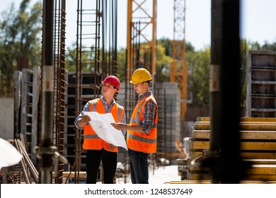 Construction manager and engineer dressed in orange work vests and hardhelmets explore construction documentation on the building site near the steel frames