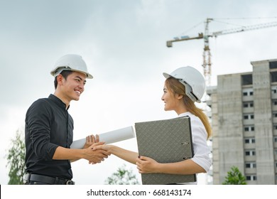 Construction manager and engineer shaking hand   on building site