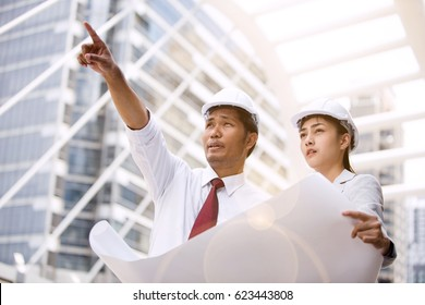 The construction manager and engineer working with a blue print at construction site