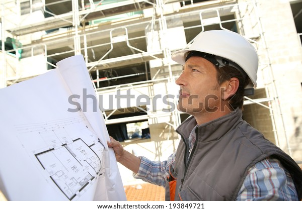 Construction manager on building site holding blueprint