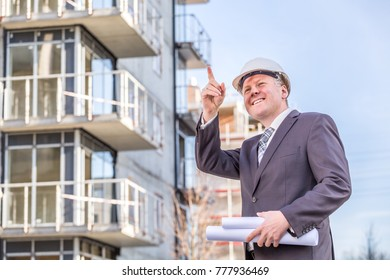 Construction worker pointing up stock photos images photography construction manager with rolled up blueprints pointing in front of construction site malvernweather Images