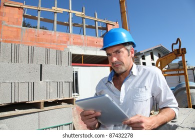 Construction manager using electronic tablet on building site