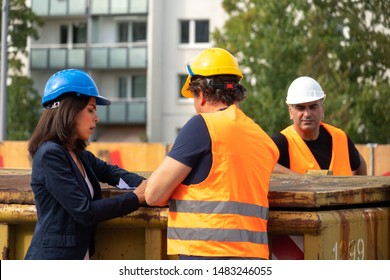 Construction manager wearing safety jacket and helmet checking projects discussing with a female engineer. In background, another worker