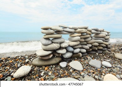 construction of many pebbles on a sea coast near water. focus on left part of construction.