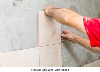 construction mason man hands on tiles work with cement mortar
