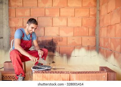 Construction mason worker, bricklayer building brick walls with spatula and mortar