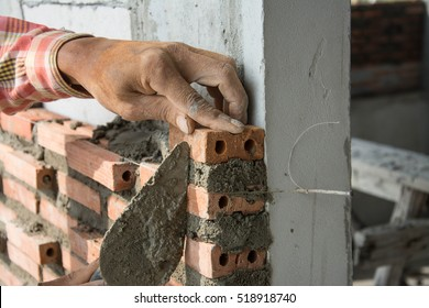 Construction mason worker with trowel and cement mortar