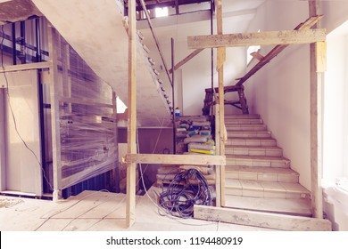 Construction materials, electrical wires, bags with cement, claircole  and putty, stairs with temporary wooden railing and elevator in an apartment is during on the construction, remodeling, overhau