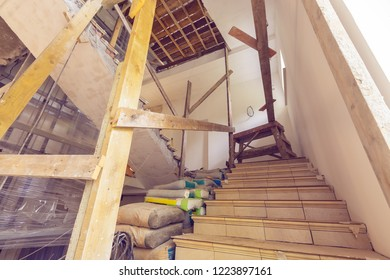 Construction materials, electrical wires, bags with cement, claircole  and putty, stairs with temporary wooden railing in  an apartment is during on the construction, remodeling, overhaul, rebuildi