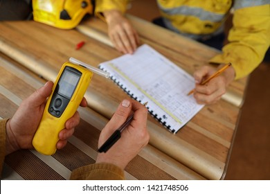 Construction miner hand holding checking at breathalyser breath alcohol testing equipment while his friend writing zero alcohol in the blood system on the daily sheet prior to work on mite site