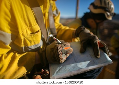 Construction miner supervisor wearing  safety glove signing working at height working permit on open field job site prior to starting high risk work each shift construction mine site Australia