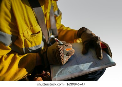 Construction miner supervisor wearing  safety glove signing working at height working permit on open field job site prior to starting high risk work each shift isolated white background