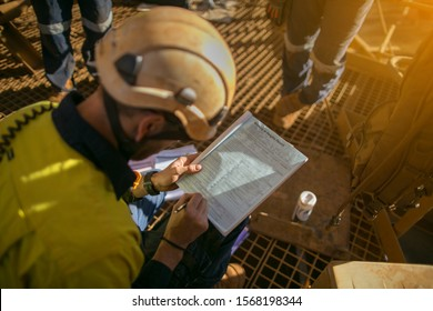 Construction miner supervisor wearing white safety helmet signing working at height working permit on open field job site prior to starting high risk work each shift construction mine site Australia