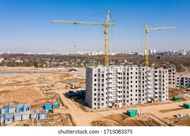 construction of new apartment building. yellow cranes against blue sky background