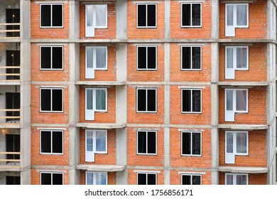 Construction of a new brick residential building with an inset of plastic modern windows