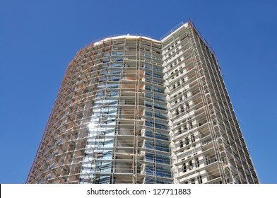 Construction of a new building with blue sky in the background and sun reflection on glass