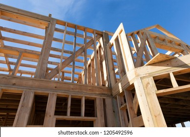 construction of a new frame house, where the frame itself is made of wooden logs and planks, closeup against a blue sky