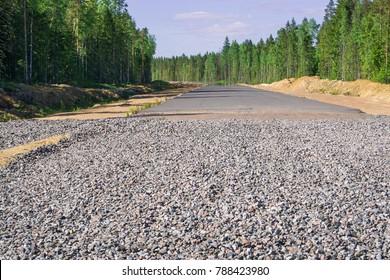 Construction of a new highway in the forest.  Asphalt paving on gravel and sand