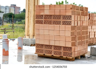 Construction of new house concept. Vertical photo red rectangular brick tray lay in stack on floor foundation outside