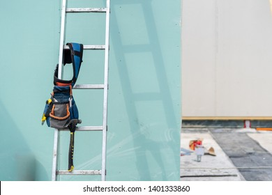 Construction new and modern modular house from composite sip panels. Toolbelt with instrument equipment on metal ladder by the wall