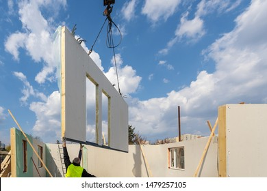 Construction new and modern modular house from composite sip panels. Worker man in uniform wear working on building development industry of energy efficient property against blue sky background