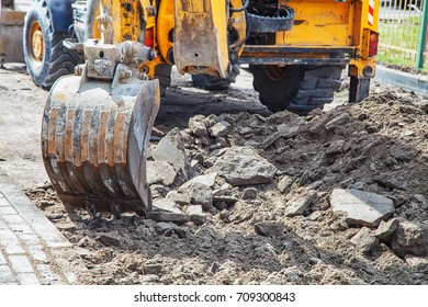 construction of a new road. excavator prepares the surface in the city on summer day. bucket closeup