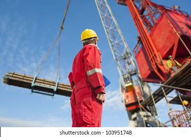 Construction operator looking at a crane carrying scaffolding materials to a super sized structure at a building site