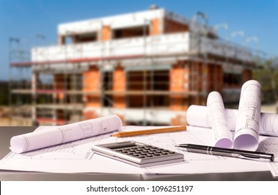 Construction plans with calculator and a shell in the background