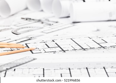 Construction plans with drawing tools on blueprints; Architectural and engineering housing concept.
