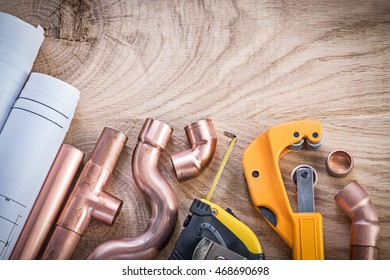Construction plans measuring tape water pipe cutter connectors on wood board plumbing concept.