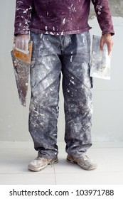 construction plastering man dirty trousers with trowel and saw in hand