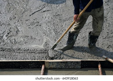 Construction pouring cement during sidewalk upgrade