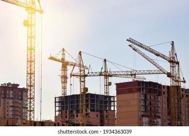 The construction process of a residential complex. Many high-rise cranes against the background of new buildings.