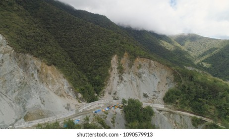 Construction of protective barriers against rock falls and landslides in the mountainous province. Aerial view of heavy machinery on the construction of a mountain road. Cement block road protection
