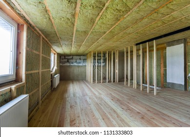 Construction and renovation of big light spacious empty room with oak floor, walls and ceiling insulated with rock wool, heating radiators under low attic windows and wooden frame for future walls.