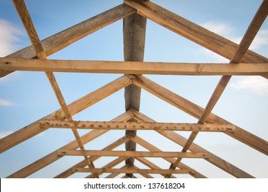 Construction of roof, wooden pine symmetric skeleton and blue sky.