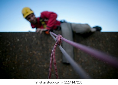 Construction rope access worker climbing up over the edge using, fasten Alpine Butterfly knot to isolated damage, cut of rope for safety precaution in high rise building, Sydney city, Australia