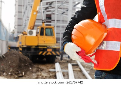 Construction safety concept, close-up worker wearing safety vest holding helmet with crane in the background