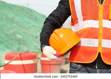 construction safety concept foreman wearing safety vest holding helmet
