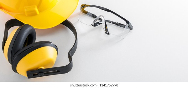Construction safety equipment including hard hat, earmuffs, and protective goggles on white background banner image with copy space