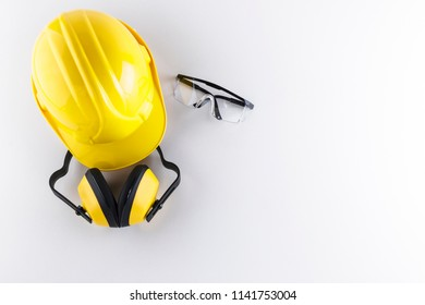 Construction safety equipment including hard hat, earmuffs, and protective goggles on white background with copy space