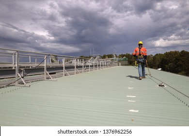 Construction safety inspector wearing fall safety harness walking on the roof by clipping safety rope on fall arrest, fall restraint   horizontal safety line while inspecting fixed roof anchor points  - Shutterstock ID 1376962256