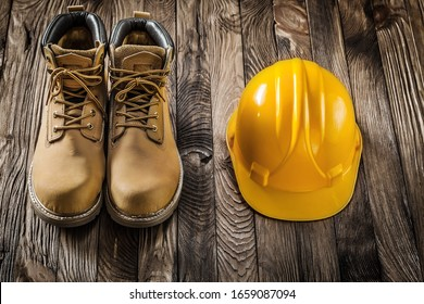 construction safety tools yellow helmet and leather working boots on vintage wooden background